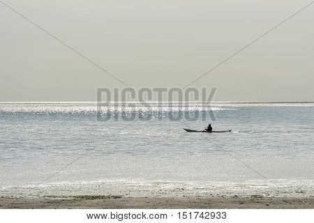 Canoeist on the Wadden Sea at Vlieland in the reflection of the sunlight of the water