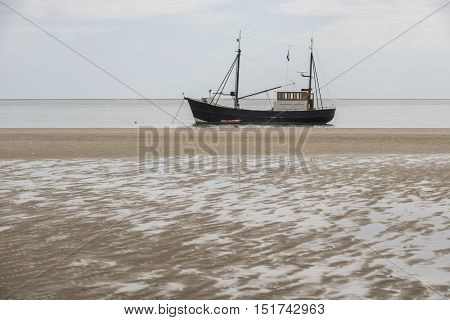Fishing boat on the beach of the Wadden Sea near the island of Terschelling in the North of the Netherlands