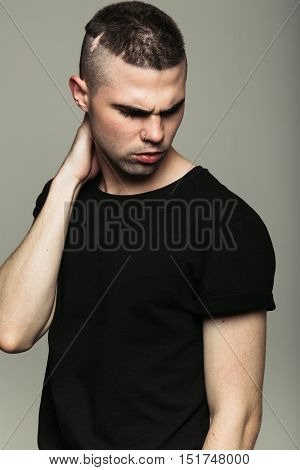 Man on grey studio background scowling at something