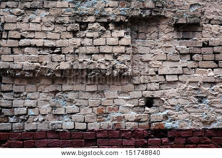 Old red brick wall in bad condition as background horizontal view closeup