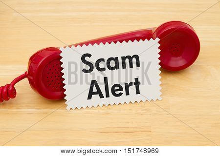Getting a call that is an scam A retro red phone with note card on a desk with text Scam Alert
