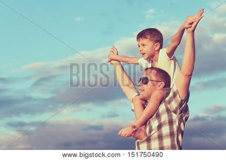Father and son playing on the beach at the day time. People having fun outdoors. Concept of friendly family.