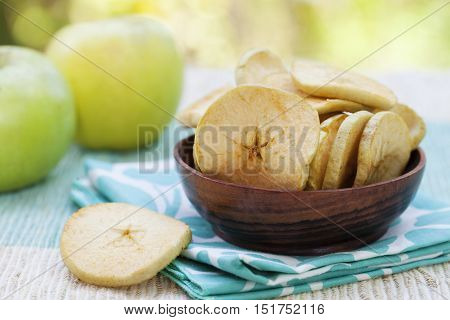 Dried dehydrated deep fried apple chips in a wooden bowl with fresh apple on tropical summer background Copy space