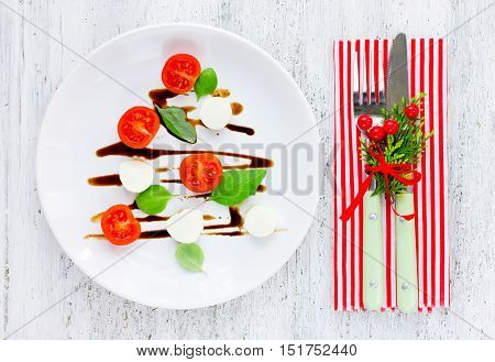 Festive Christmas appetizer caprese salad shaped Christmas tree. Christmas table setting with decorations