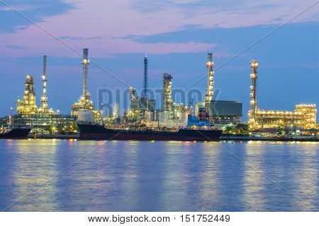 Oil refinery light night view river front with beautiful twilight sky background