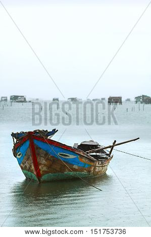 fishing wooden boat in the sea water near the shore.