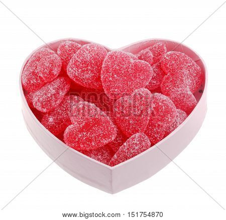 Pink heart shaped box filled with heartshaped jellly candy with a taste of strawberry isolated on white.
