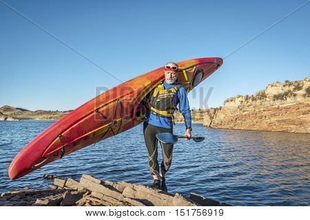senior male is carrying  a colorful river kayak on a rocky lake shore Horsetooth Reservoir) - recreation concept