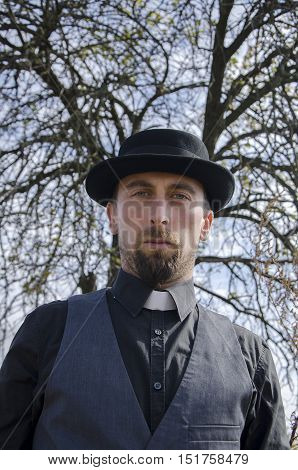 Young bearded priest in hat on tree background
