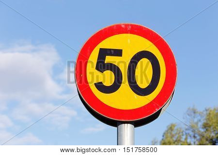 Road sign on pole speed limit 50 with black digits ob yellow background and red border on blue sky.