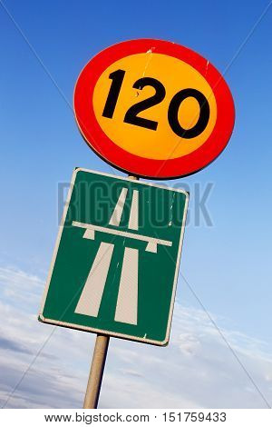 Swedish road signs speed limit 120 and motorway on blue sky with clouds.