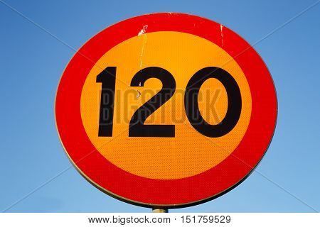 Swedish speed limit 120 km/h road sign on blue background.