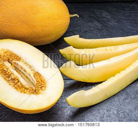 slices of melon half melon and whole melon on the black table