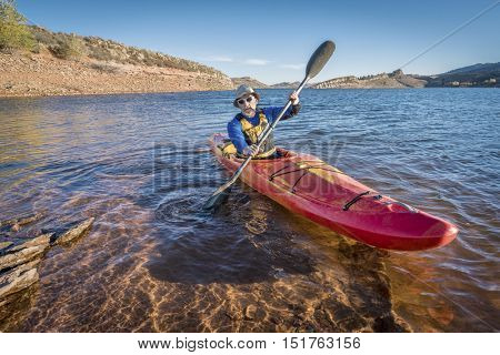 senior male is paddling colorful river kayak on a calm lake Horsetooth Reservoir) - recreation concept
