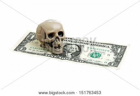 A skull placed on a american dollars isolated on white background.