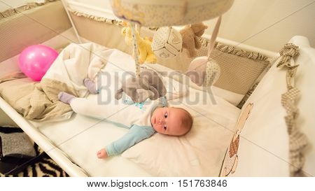 Baby lying in his cot and playing with Crib Mobiles