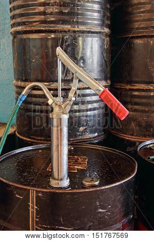 Manual pump on black oil flank taken closeup.