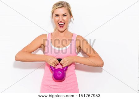Happy Blonde Woman Working Out With Kettlebell