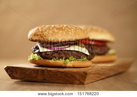 two homemade burgers on olive board on oak table, shallow focus