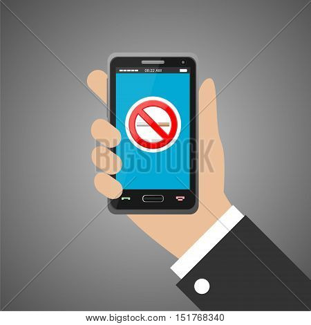 Hand holding smartphone with no smoking sign on gray background