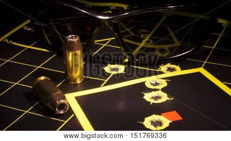 Safety glasses and pistol cartridges on a target with holes
