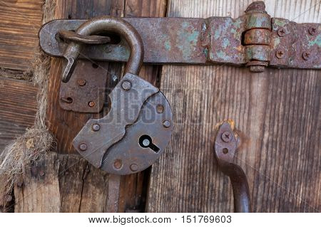 Old rusty padlock and latch on a wooden door with rusty nails