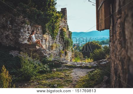 Attractive woman in Stari Bar ancient fortress, Montenegro. Brunette girl with long hair in dress walks around the old castle, the magic atmosphere of magic and fairy tales.