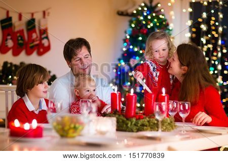 Big family with three children celebrating Christmas at home. Festive dinner at fireplace and Xmas tree. Parent and kids eating at fire place in decorated room. Child lighting advent wreath candle.