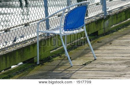 Fisherman's chair on a pier without the fisherman present. poster
