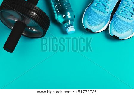 Fitness background made of sneakers, bottled water and fitness wheel on blue background. Concept of healthy lifestile and food, everyday training and force of will. Flat lay style of picture