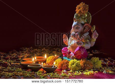 Clay diya lamps lit with Lord Ganesha during Diwali Celebration. Greetings Card Design Indian Hindu Light Festival called Diwali