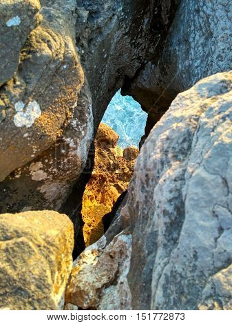 Hole to the ocean in rocks in sunset light near Cabo Carvoeiro, Peniche, Portugal