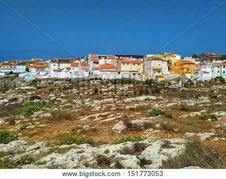 Colorful houses close to rocks on the ocean coast in Peniche, Portugal