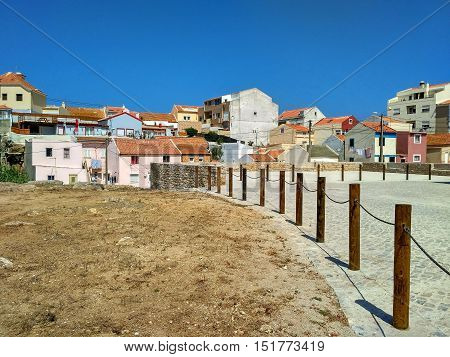 View to houses near ocean from wooden road in Peniche, Portugal