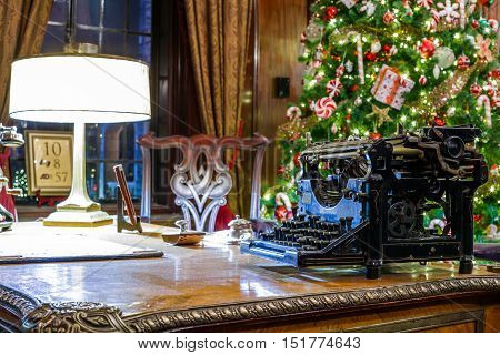 Old typewriter and christmas interior. Christmas tree on the background