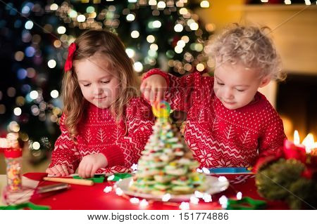 Little boy and girl making Christmas gingerbread house at fireplace in decorated living room. Kids playing with ginger bread under Christmas tree. Baking and cooking with children for Xmas at home. Focus on girl