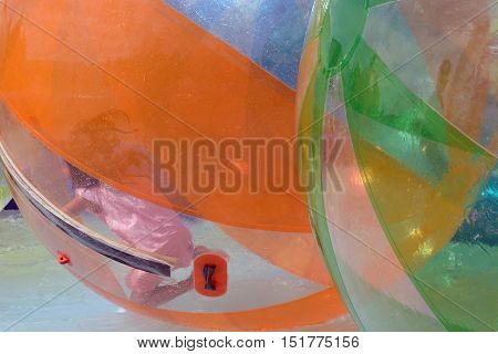 Unrecognizable girl inside huge water orb ball in pool