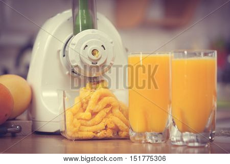 Making orange juice nutritious vitamin packed drink in juicer machine at home in kitchen. Healthy eating vegetarian food dieting concept