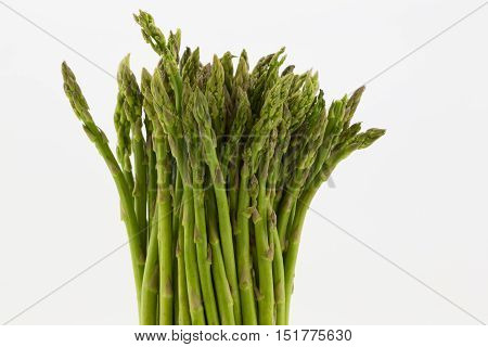 Fresh asparagus stalks in upright position agains white background. Horizontal image with copy space on right.