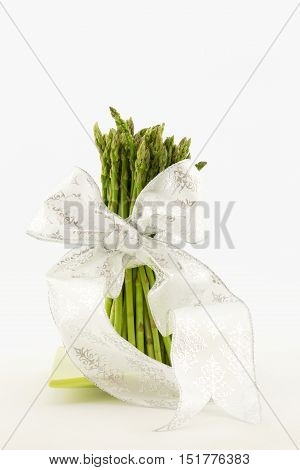Vertical photo of asparagus stalks tied with white ribbon. Still life with white background and copy space.