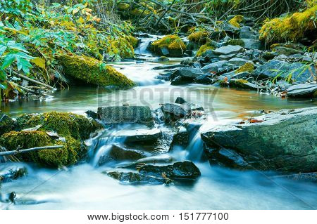 River flowing through stony bottom. Beautiful waterfall landscape. The water stream flowing over rocks. Beautiful mountain river landscape.