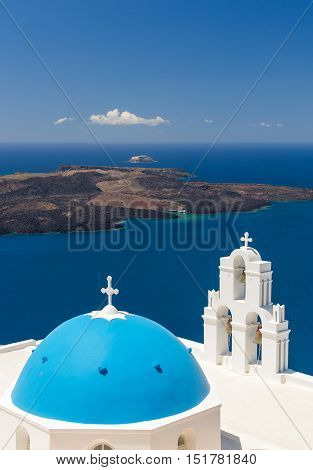 Blue-domed chapel with ochre bell tower in Oia Santorini Greece with ocean behind