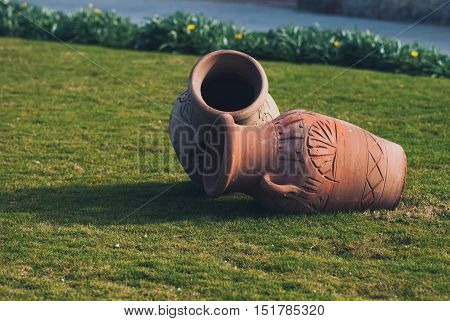 Two Clay amphora jug, old ceramic vases on green grass lawn near sea.