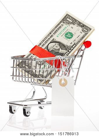 US Dollars wrapped with a red satin ribbon with an attached price tag in a shoping cart isolated on white background.