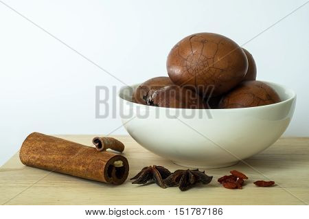 Tradional chinese herbs on chopping board and herbal eggs in a white bowl