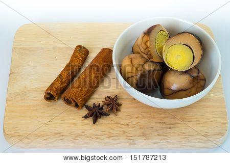 Tradional chinese herb on chopping board and herbal eggs in a white bowl