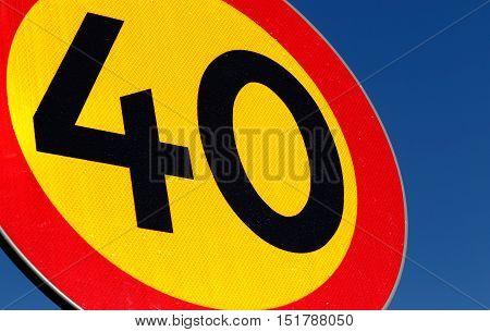 Close-up of a Swedish speed limit 40 kmh road sign on blue sky.