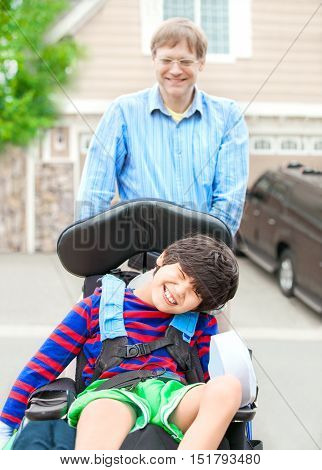 Caucasian father pushing disabled biracial ten year old son in wheelchair outdoors. Child has cerebral palsy.