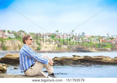 Caucasian man in mid forties sitting by water's edge with rocky cliff in background hugging bent knee and looking out over water