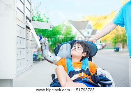 Disabled ten year old boy in wheelchair reaching up to get mail from mailbox outdoors